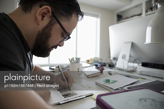 Focused male illustrator sketching in home office - p1192m1567448 by Hero Images
