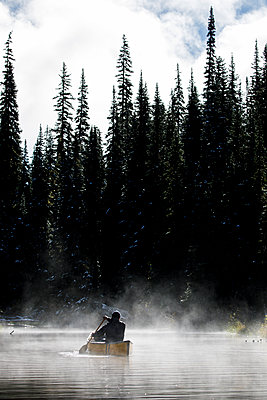Rear view of man canoeing in lake against fog and trees - p1166m2235073 by Cavan Images