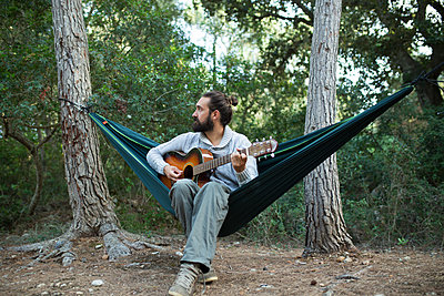 Man sitting in hammock playing guitar in the woods, partial view - p300m2060195 by Sus Pons