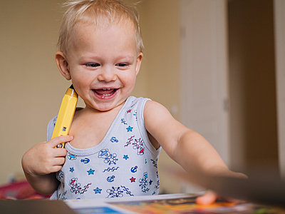 Cheerful baby boy playing with pencil at home - p300m2206831 by Konstantin Trubavin