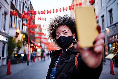Woman wearing protective face mask taking selfie during vacations at Chinatown during COVID-19 - p300m2273653 by Angel Santana Garcia