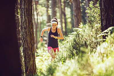 Active female athlete running in forest - p300m2282632 by Mikel Taboada