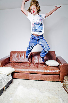 Boy jumping on a sofa - p9070013 by Anna Fritsch