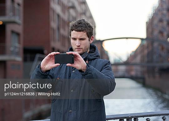 Mann fotografiert in der Speicherstadt - p1124m1216838 von Willing-Holtz