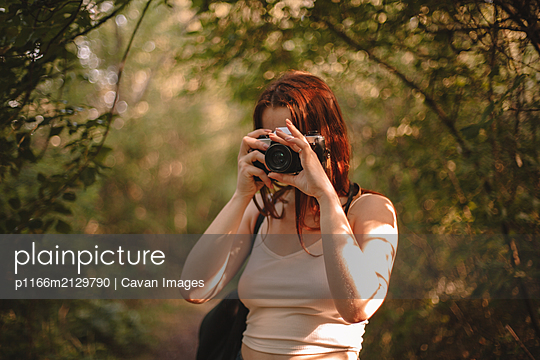 Woman photographing with camera in forest - p1166m2129790 by Cavan Images