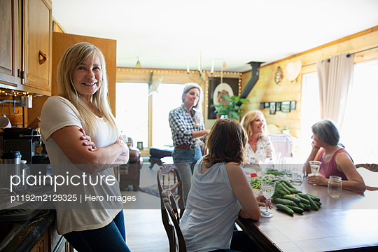Portrait of senior woman in kitchen with friends - p1192m2129325 by Hero Images
