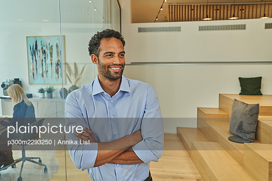 Male professional looking away with arms crossed while leaning on glass wall at office - p300m2293250 by Annika List