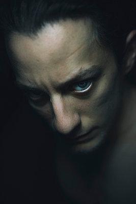 Junger Mann im Dunkeln starrt in die Kamera - p1180m1028178 von chillagano