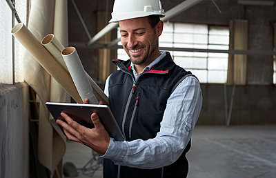 Smiling building contractor using digital tablet while standing at construction site - p300m2243425 by Veam