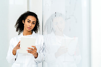 Confident female researcher holding digital tablet while leaning on whiteboard in laboratory - p300m2265594 by Giorgio Fochesato