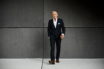 Confident businessman with hand in pocket walking against gray wall - p300m2277457 by Sandro Jödicke