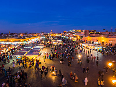 Africa, Morocco, Marrakesh-Tensift-El Haouz, Marrakesh, View over market at Djemaa el-Fna square in the evening - p300m949713f by Martin Moxter