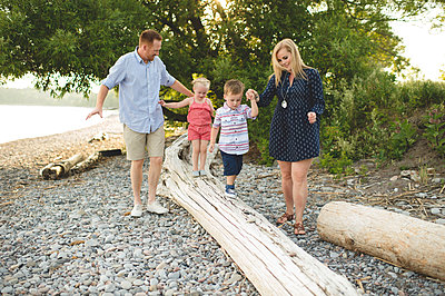 Mid adult parents holding hands with boy and girl on tree trunk at Lake Ontario, Oshawa, Canada - p429m1175253 by Erin Lester