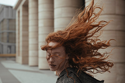 Wind blowing hair of Caucasian woman near pillars - p555m1531628 by Ivan Ozerov