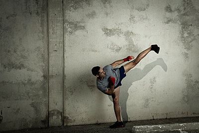 Kickboxer, in urban environment, in fighting stance - p924m1230281 by Wil Cohen