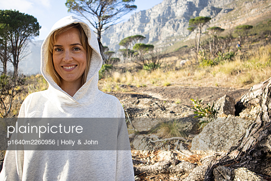 Woman with hooded shirt in mountain landscape - p1640m2260956 by Holly & John