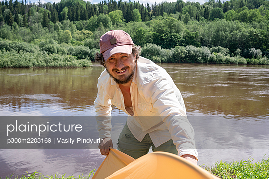 Smiling mid adult man installing tent while standing against lake in forest - p300m2203169 by Vasily Pindyurin