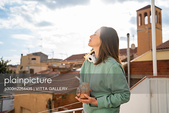 Woman with eyes closed holding fruit smoothie while standing at balcony - p300m2264435 by VITTA GALLERY