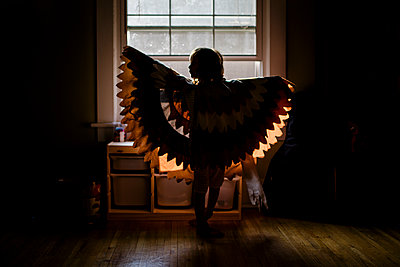 A small girl stands silhouetted in a window wearing outstretched wings - p1166m2182925 by Cavan Images