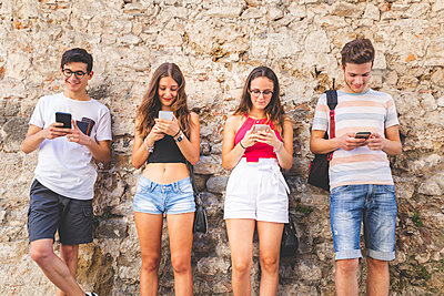 Group of friends standing at a wall using their cell phones - p300m2062918 by William Perugini