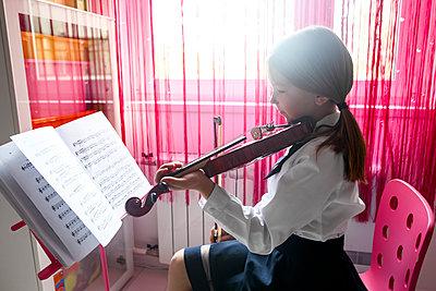 Girl sitting at the window at home playing violin - p300m2102895 by Ekaterina Yakunina