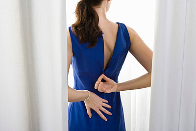 A woman trying on a dress - p3018897f by Paul Hudson