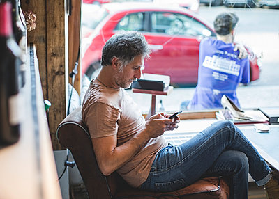 Mature owner using mobile phone while sitting on chair in deli - p426m2045893 by Maskot