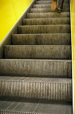 Man walking up an escalator (part of), selective focus - p4901235 by Felbert & Eickenberg