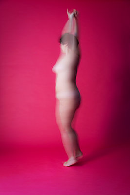 Naked woman in studio, blurred on pink background - p590m2054314 by Philippe Dureuil
