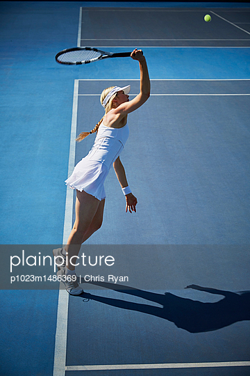 Young female tennis player playing tennis, reaching with tennis racket on sunny blue tennis court