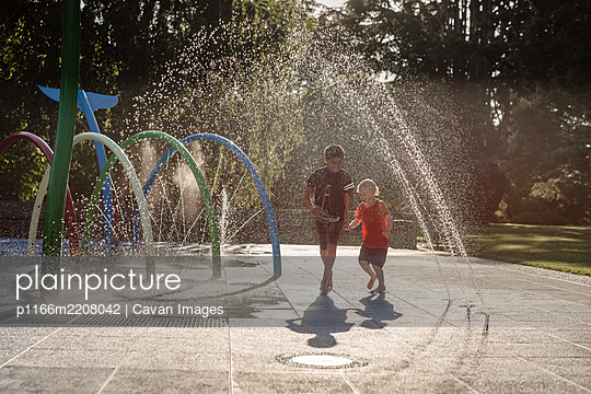 Brothers running in water at playground in New Zealand - p1166m2208042 by Cavan Images