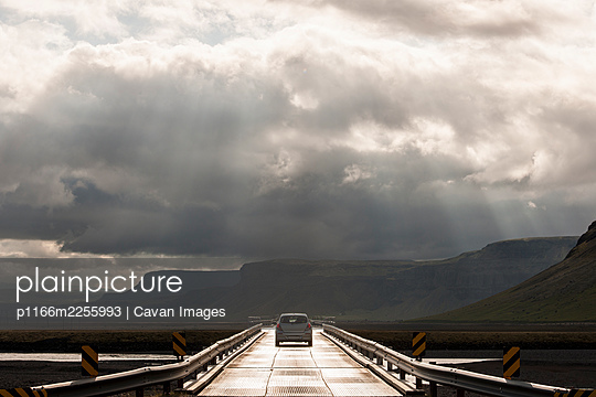 car driving over SkeiÌ¡arÌÁrsandur on the longest bridge in Iceland - p1166m2255993 by Cavan Images