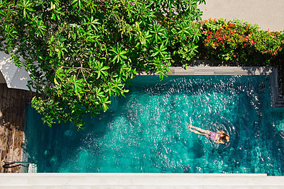 High angle view of girl swimming in pool during sunny day - p1166m2025230 by Cavan Images