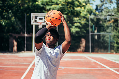 Portrait of an African-American black boy playing basketball on an urban court. - p1166m2280306 by Cavan Images