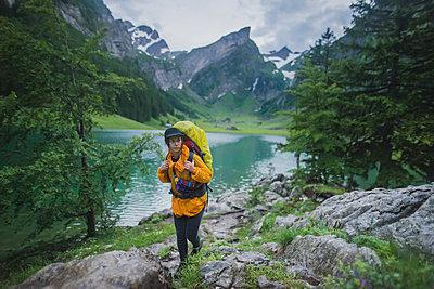 Woman wearing yellow hiking by Seealpsee lake in Appenzell Alps, Switzerland - p1427m2146887 by Oleksii Karamanov