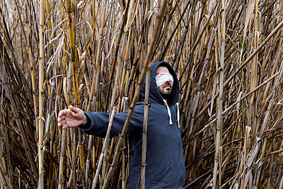 Blindfolded man in the reeds - p1521m2157614 by Charlotte Zobel