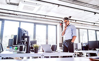 Mature businessman looking at laptop on desk in office - p300m1568077 by HalfPoint