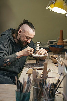 Potter working on a tiny figurine in workshop - p300m2167586 by Vasily Pindyurin