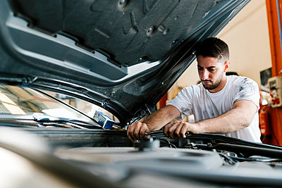 Young man repairing car while standing in auto repair shop - p300m2220695 by Ezequiel Giménez