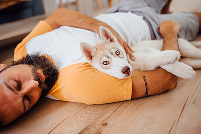 Man resting with puppy on floor at home - p300m2243862 by Miguel Frias