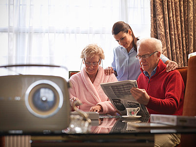 Nurse reading with older couple - p42918077f by Monty Rakusen