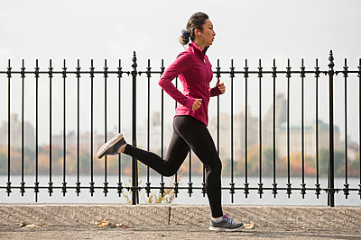 Asian woman running on waterfront path - p555m1414396 by JGI/Tom Grill