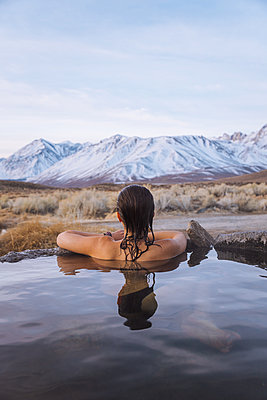 Woman enjoying hot spring in cold winter, Mammoth Lakes  Hot Spring, California, USA - p924m2153131 by Danielle Rodriguez