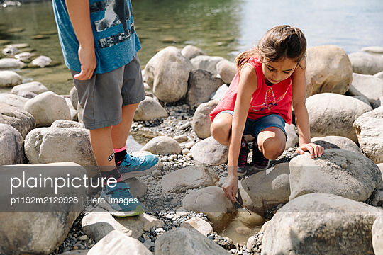 Two children playing on riverbank - p1192m2129928 by Hero Images