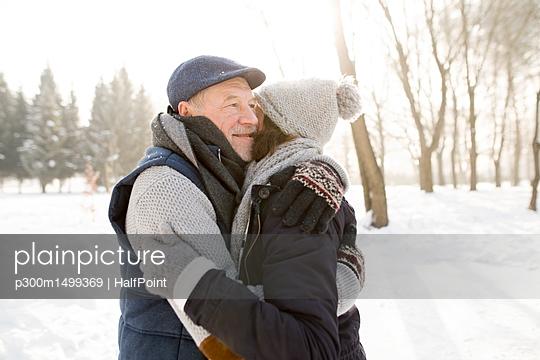 Happy senior couple hugging in winter landscape