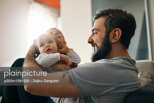 Happy father with baby girl and little son together at home - p300m1581526 von Zeljko Dangubic