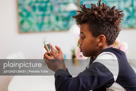 Boy using cell phone - p312m2139431 by Pernille Tofte