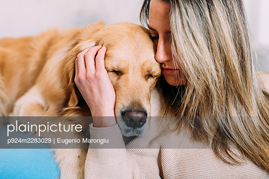 Italy, Young woman with dog at home - p924m2283029 by Eugenio Marongiu