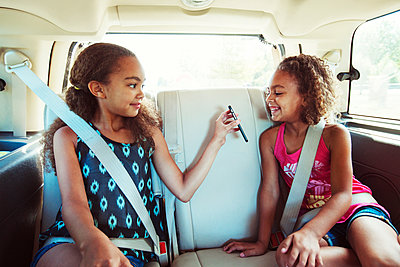 Girl showing smart phone to sister while traveling in car - p1166m1225972 by Cavan Images