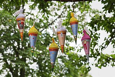 Einschulungstüten hängen im Baum - p1519m2124730 von Soany Guigand